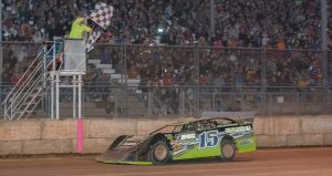 Nick Anvelink takes the checkered flags in front of an overflowing crowd after leading all 30 laps of the M.J. McBride Memorial at Shawano Speedway on April 16. (Shawn Fredenberg photo)